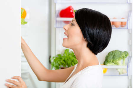 seeks: Woman seeks food in the opened fridge full of vegetables and fruit. Concept of healthy and dieting food