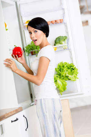 takes: Woman takes sweet pepper from the opened fridge full of vegetables and fruit. Concept of healthy and dieting food