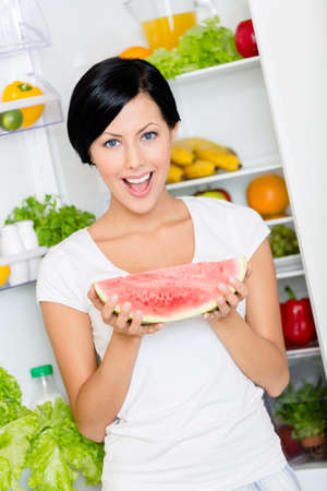Woman takes watermelon from the opened fridge full of vegetables and fruit. Concept of healthy and dieting food photo