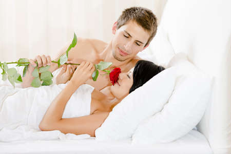 gives: Man lying in bed-room gives red rose to woman. Concept of love and affection Stock Photo