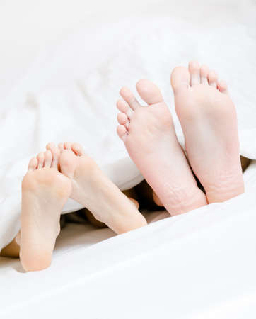 lying in bed: Close up of two pairs of feet of the couple next to each other in bed