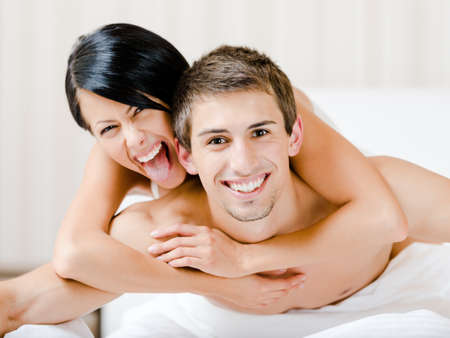 Close up of laughing couple who plays in bedroom. Woman lying on the back of the man embraces him photo