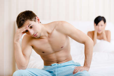 Young couple argues in bed. Depressed male sitting on the edge of the bed. Focus on man Stock Photo