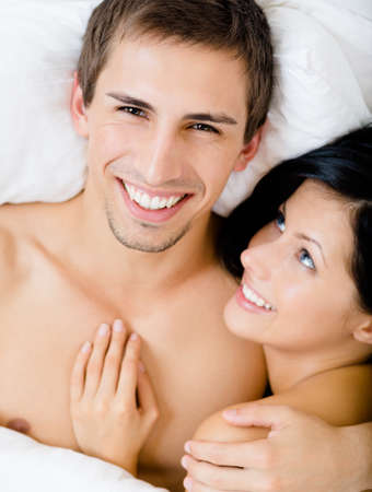 Close up view of couple lying in bed, top view. Concept of love and affection photo