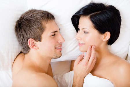 Close up of man stroking woman lying in bedroom, top view. Concept of love and affection photo