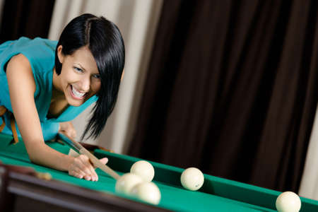 avocation: Girl playing billiard. Spending free time on gambling