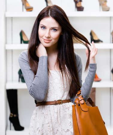 comprando zapatos: Retrato de la mujer en el centro comercial en la sección de zapatos de tacón alto femeninos. Concepto de consumismo y compra con estilo