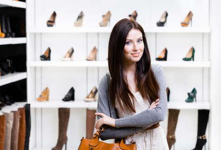 Portret van vrouw in winkelcentrum in de sectie van de vrouwelijke pompen. Concept van het consumentisme en stijlvolle aankoop