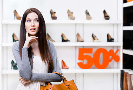 Portrait of woman in shopping center with 50% sale in the section of female high heeled shoes. Concept of consumerism and stylish purchase photo