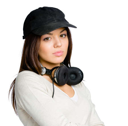 Teenager in black peaked cap wearing earphones, isolated on white photo