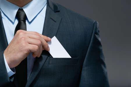 cerrar: Parte de la carrocería del hombre de negocios que lleva a cabo la tarjeta de visita del bolsillo de traje de negocios, copyspace Foto de archivo