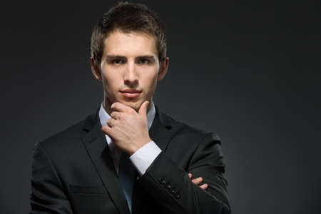 Portrait of pensive man wearing business suit and black tie touches his face photo
