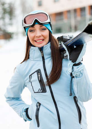 vertical format: Half-length portrait of girl wearing sports jacket and goggles who hands skis Stock Photo