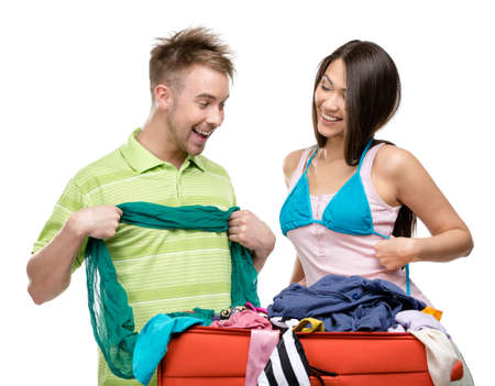 Couple packs suitcase with clothing for traveling, isolated on white. Concept of romantic vacations and lovely honeymoon photo
