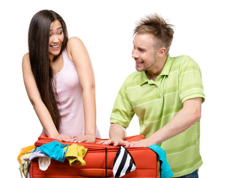 Couple packs up suitcase with clothing for journey, isolated on white. Concept of romantic vacations and lovely honeymoon photo