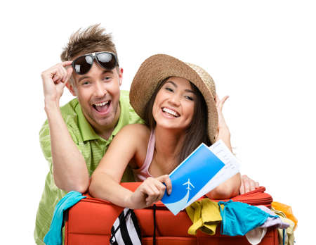 Couple packs up suitcase with clothing for departure, isolated on white. Concept of romantic vacations and lovely honeymoon photo