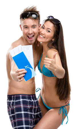 Half-length portrait of half-naked couple with travel tickets, isolated. Concept of romantic vacations and lovely honeymoon photo