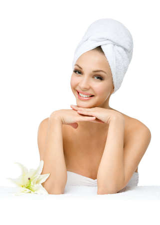 Girl with towel on head touches face sitting near a white lily, isolated on white. Concept of healthcare, beauty and youth photo