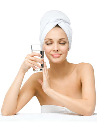 Girl with eyes closed and with towel on head hands glass of water, isolated on white. Concept of healthcare, beauty and youth photo