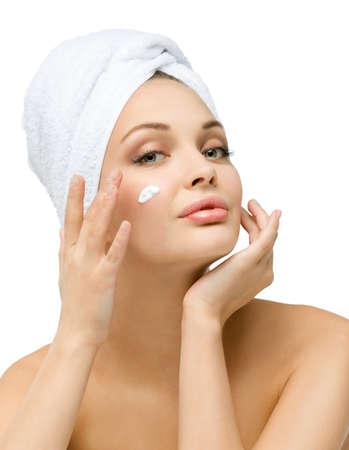 Muchacha con la toalla en la cabeza se aplica crema en la cara, aislado en blanco. Concepto de salud, belleza y juventud Foto de archivo - 22279607