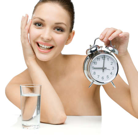 Girl with glass of water shows alarm clock, isolated on white photo