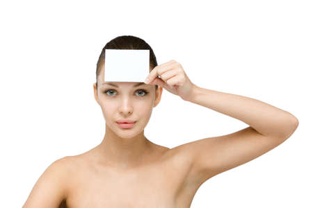 Girl hands white and blank copyspace card in front of her forehead, isolated on white photo