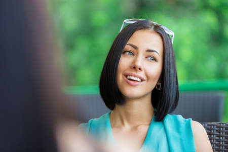 adult intercourse: Girl wearing blue dress and sunglasses sits at the table of the bistro and talks with friend Stock Photo