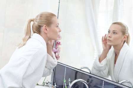 Woman in bathrobe looks at the mirror in bathroom photo