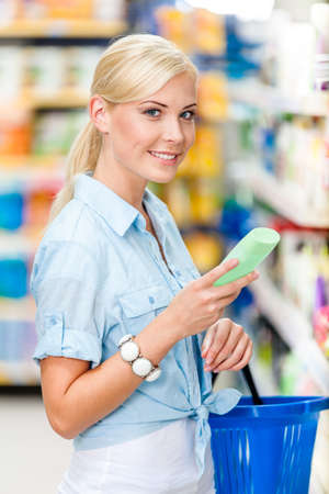Half length portrait of girl at the store choosing cosmetics among the great variety of products. Concept of consumerism, retail and purchase Stock Photo - 22528181