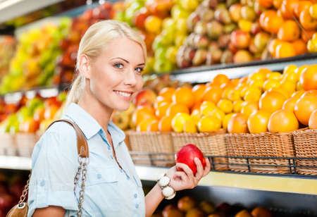 Girl at the shopping center choosing fruits and vegetables hands fresh red apple photo