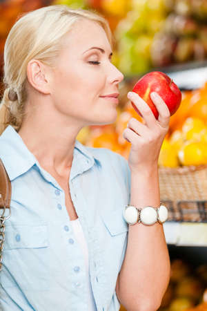 smells: Girl at the shop choosing fruits and vegetables smells fresh red apple while her eyes are closed Stock Photo