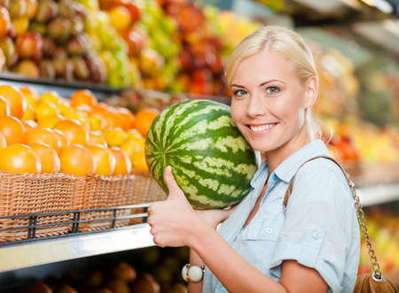 Girl at the market choosing fruits and vegetables hands watermelon thumbs up photo