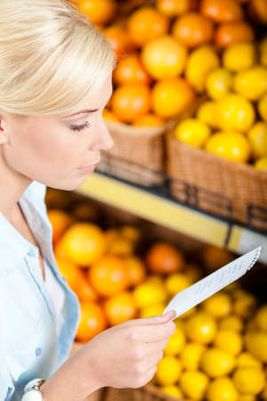 Girl looks through shopping list near the stack of fruits lying in the braided baskets in the market Stock Photo - 22528198
