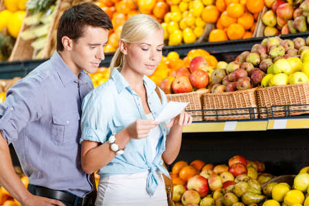 decides: Happy couple with shopping list against the piles of fruits decides what to buy