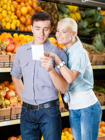 decides: Happy couple with shopping list against the heaps of fruits decides what to buy