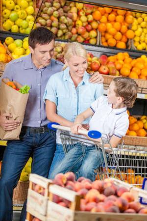 Glückliche Familie gegen Regalen der Früchte geht einkaufen. Vater hält eine Tüte mit Obst und Sohn sitzt im Warenkorb
