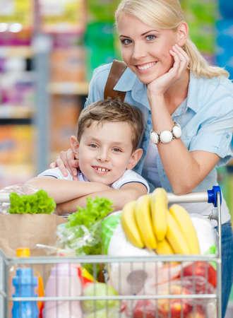Mutter und Sohn mit Warenkorb voller Produkte in Einkaufszentrum. Konzept der gesunden Ernährung und Konsum