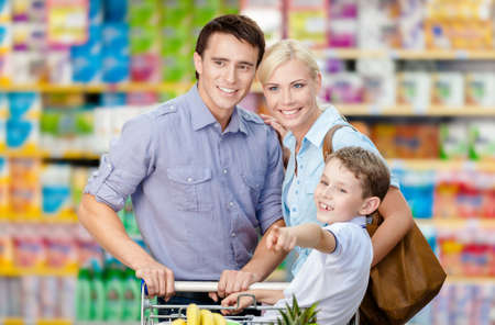 Half-length portrait of family in the shop. Concept of consumerism and family relations photo