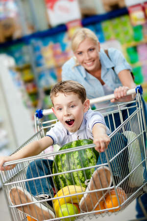 Little boy sits in the shopping trolley with watermelon and other products while mother drives it