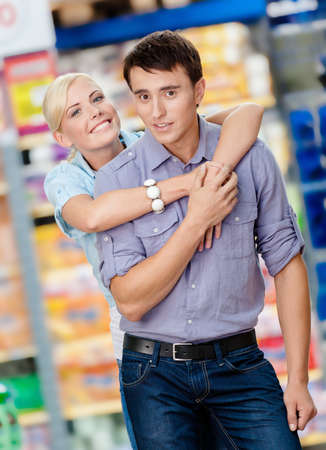 Girl embraces man in the market. Concept of happy relationship and affection photo
