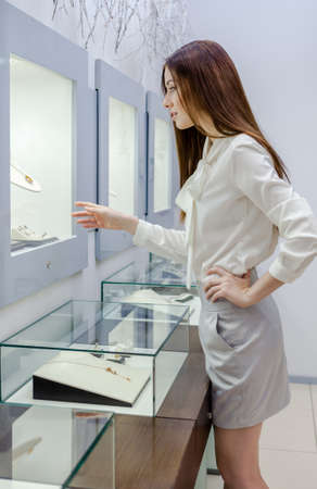 Half-length portrait of girl looking at jewelry in showcase at jewelers shop. Concept of wealth and luxurious life photo