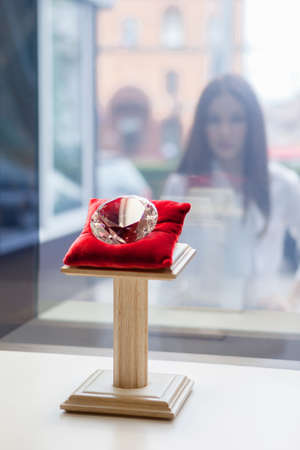 Girl looking at the diamond through the window at jewelers shop. Concept of wealth and luxurious life photo