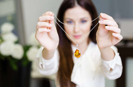 platinum hair: Woman keeping necklace with yellow sapphire at jewelers shop. Concept of wealth and luxurious life