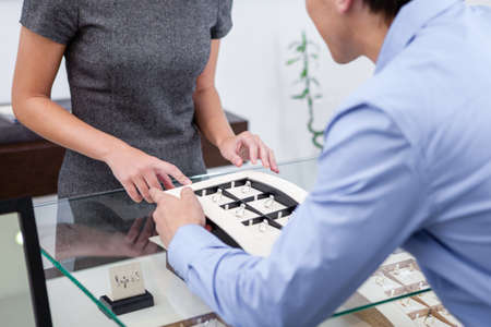Male selecting engagement ring at jewelers shop. Concept of wealth and luxurious life photo