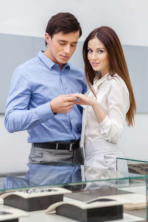 long shot: Man presents engagement ring to his woman at jewelers shop. Concept of wealth and luxurious life