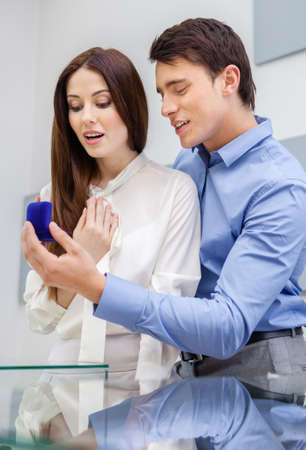 Male presents engagement ring to his woman at jewelers shop. Concept of wealth and luxurious life photo