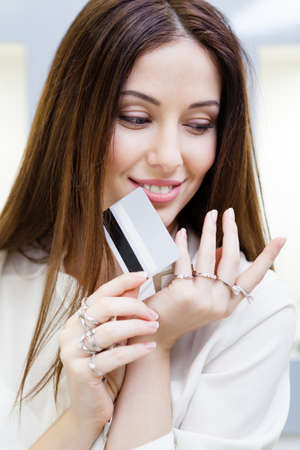 Woman with lots of rings on hands keeps credit card. Concept of wealth and luxurious life photo