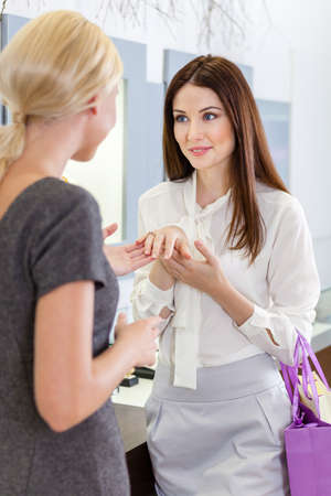 Two girls discuss engagement ring at jewelers shop. Concept of wealth and luxurious life photo