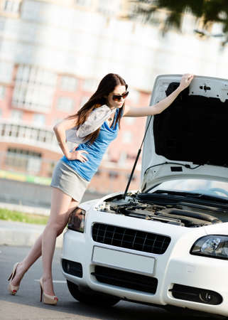 Woman repairing the broken car on the road. Girl stands near opened hood of the car after an accident photo