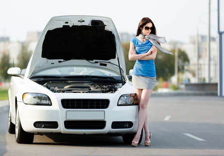 Woman with the arms crossed near the opened bonnet of the broken car waiting for assistance